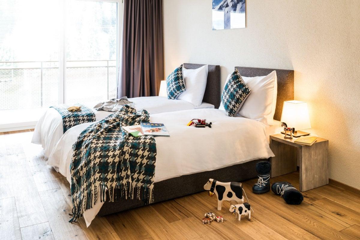 Innenansicht einen Zimmers mit getrennten Betten im Peaks Place in Laax