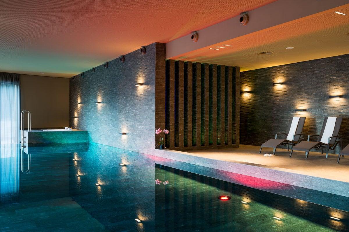Pool mit Liegen im Peaks Place Aparthotel in Laax