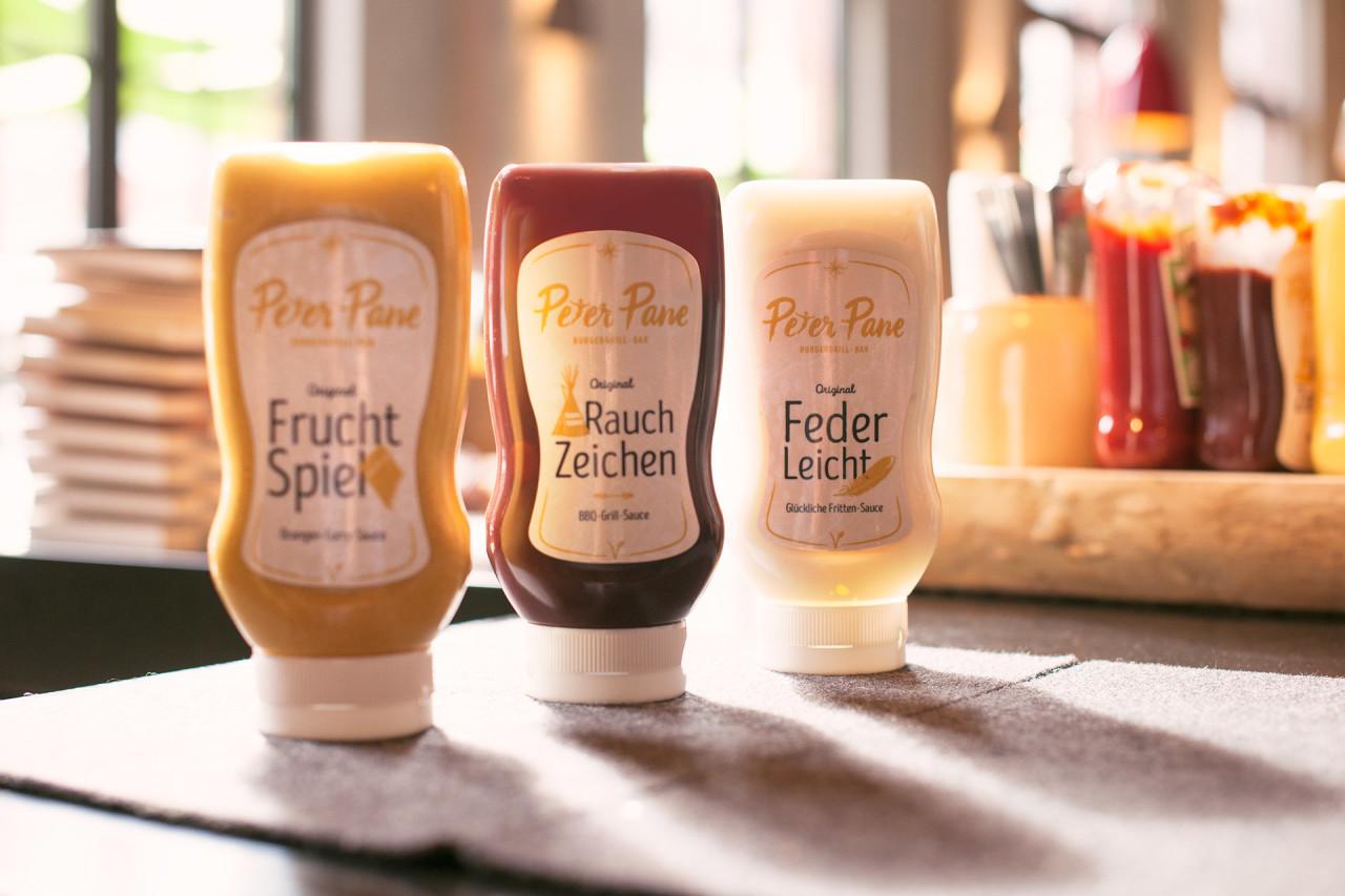 Verschiedene Saucen mit neu designten Aufklebern auf dem Tisch im Peter Pane Burgergrill und Bar