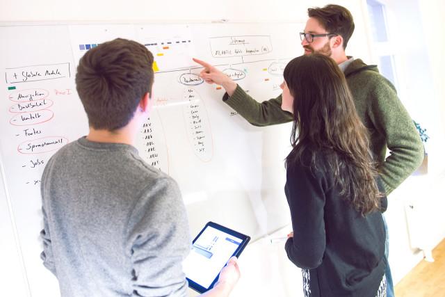 Entwickler von Redeleit und Junker während der Arbeit an der Sitemap für die ATLANTIC Hotels Website an einem Whiteboard