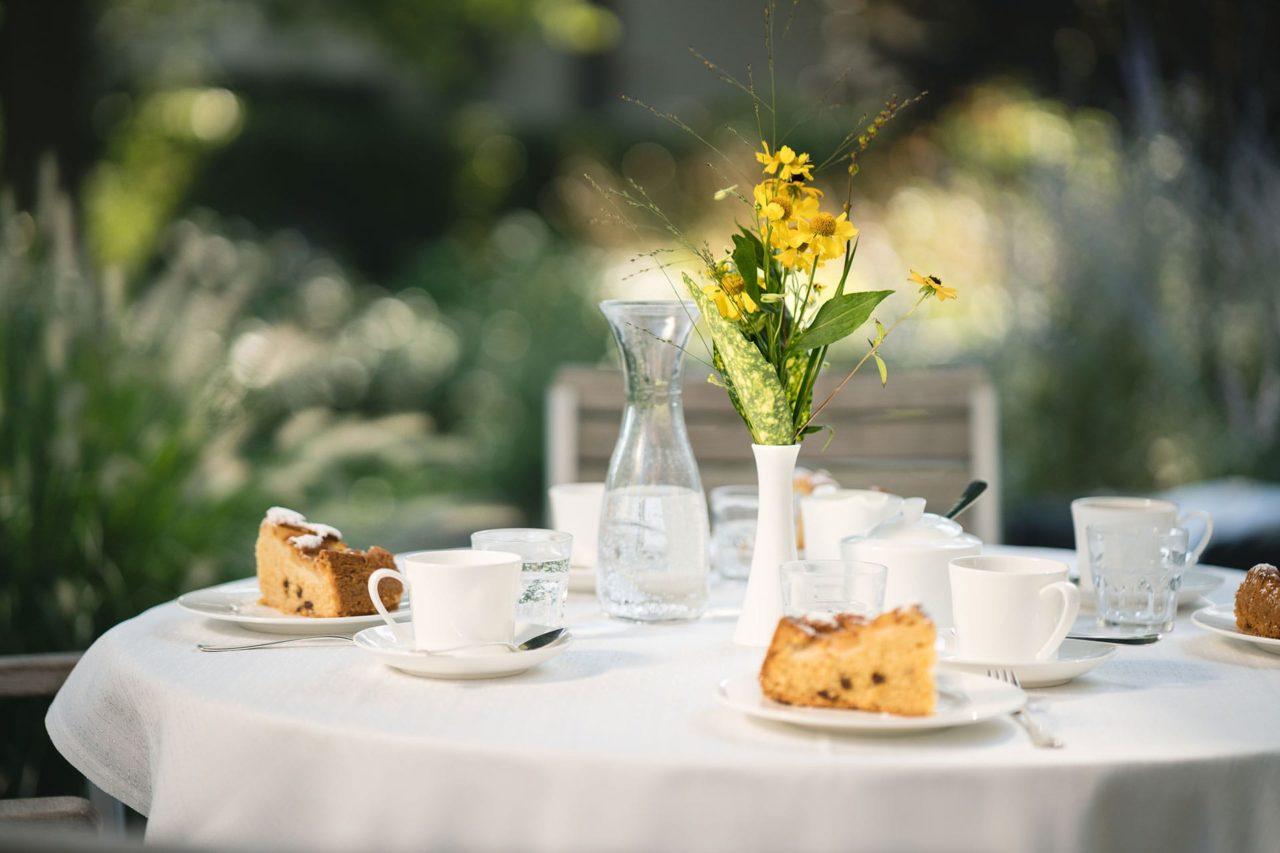 Tisch mit Kaffee und Kuchen, Blume im Landhaus Pflege und Wohnen Hannover Fotografie Redeleit und Junker