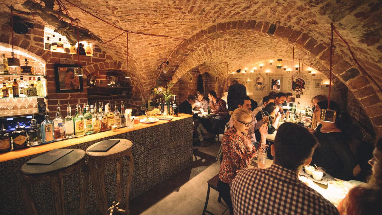 Innenraum des Sa Bacca mit Blick auf die reich ausgestattete Bar und Gäste an den Tischen