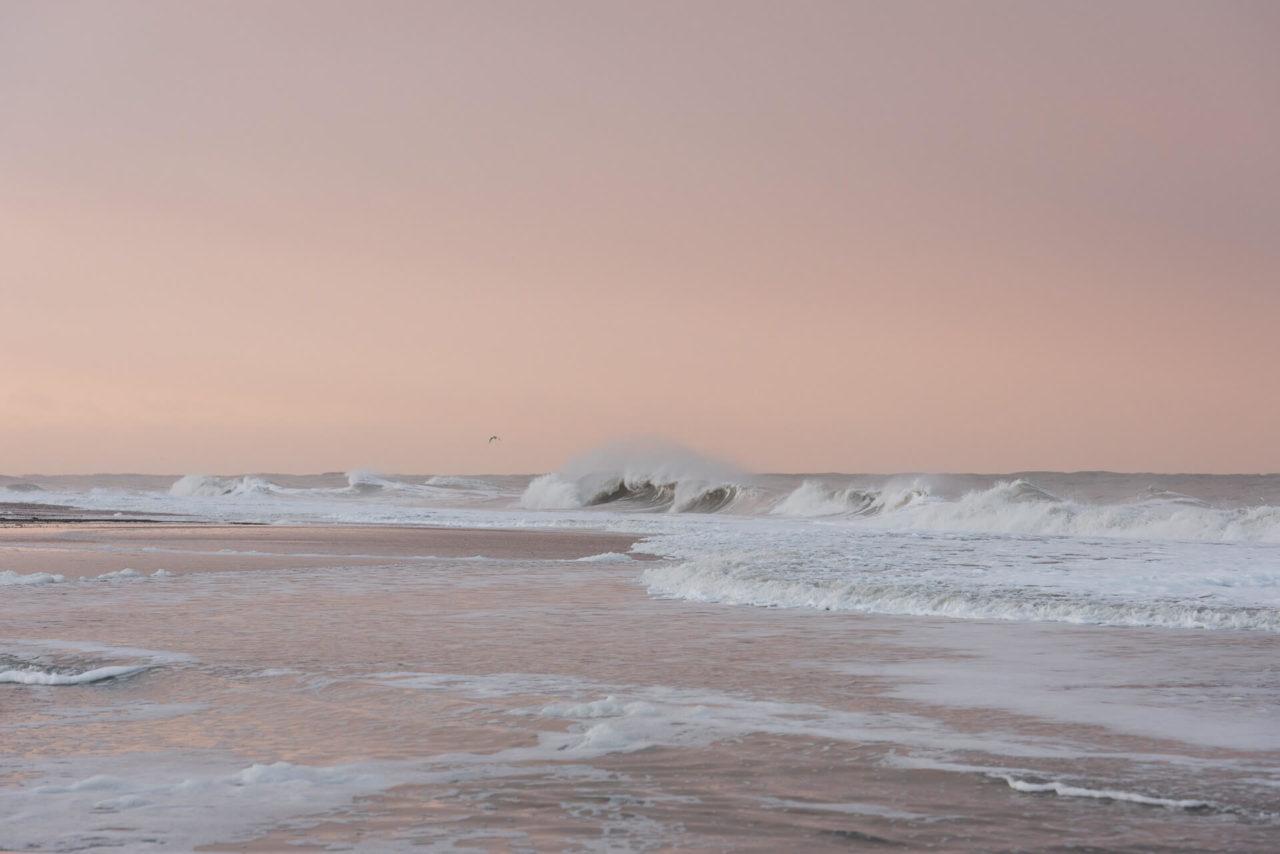 Foto von der Fotostory Redeleit und Junker zeigt eine brechende Welle beim Sonnenaufgang am Meer