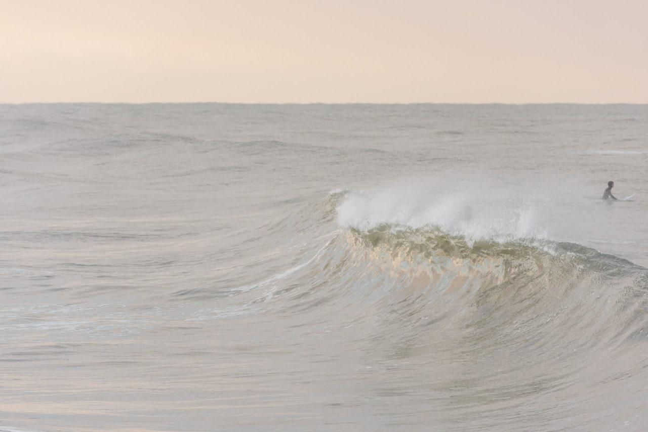 Foto von der Fotostory Redeleit und Junker zeigt eine brechende Welle und einen Surfer