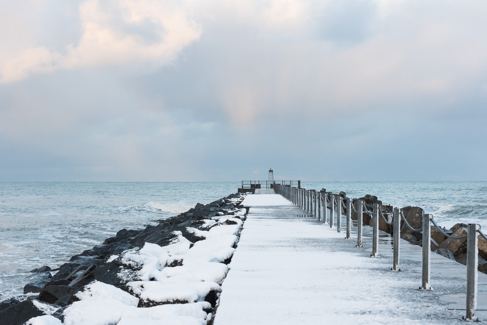 Foto von der Fotostory Redeleit und Junker zeigt eine verschneite Mole mit Blick auf das Meer