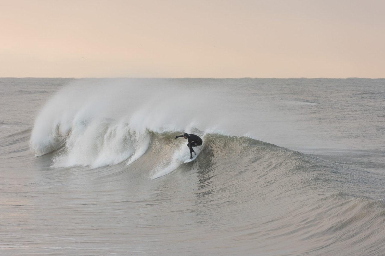 Foto von der Fotostory Redeleit und Junker zeigt einen Surfer bei einem Takeoff in einer Welle