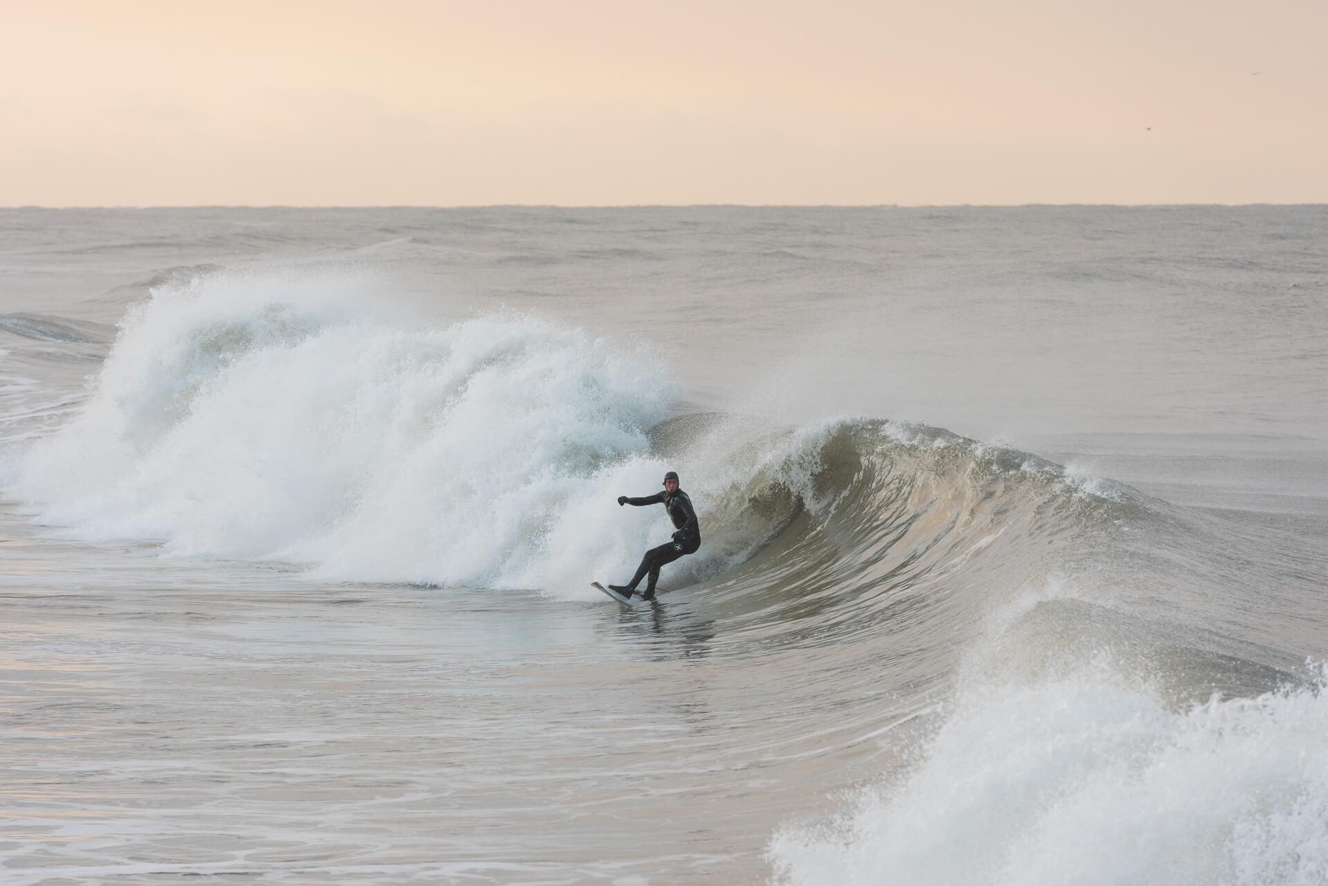Foto von der Fotostory Redeleit und Junker zeigt einen Surfer in einer Welle surfend
