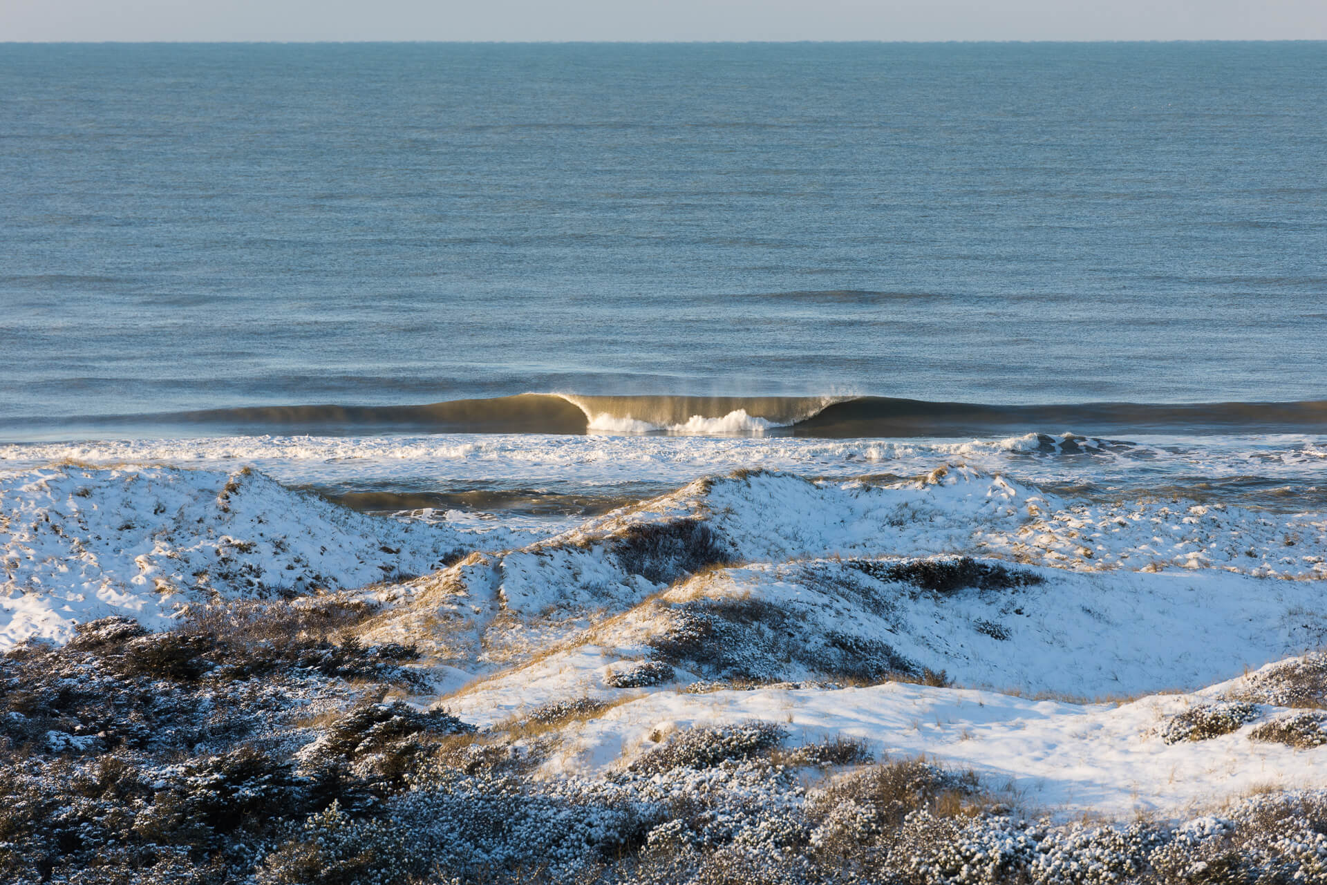 Foto von der Fotostory Redeleit und Junker zeigt eine brechende Welle und Dünenlandschaft
