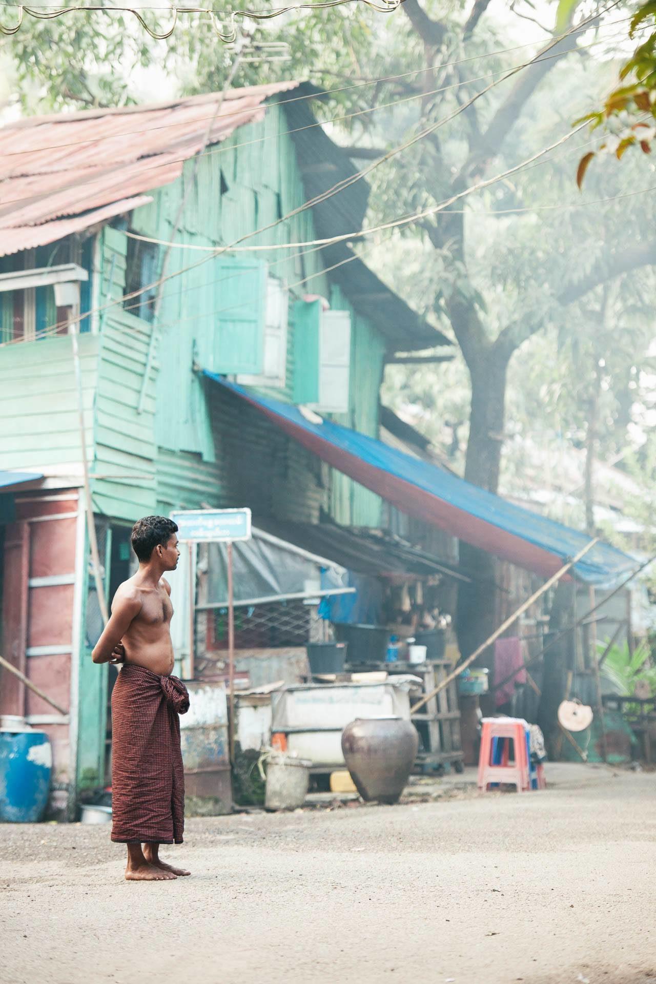 Mann, oberkörperfrei, vor Haus Myanmar Fotostory von Redeleit und Junker