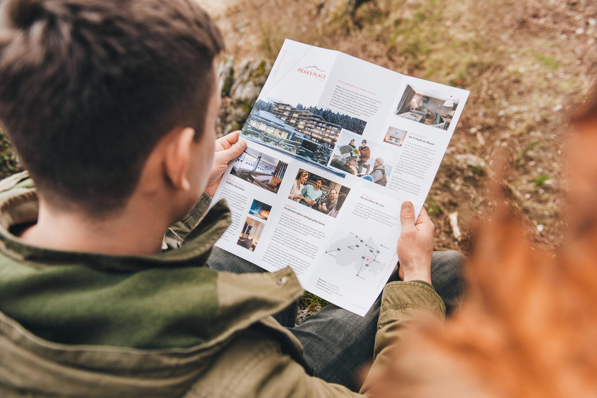 Geöffneter Flyer des Peaks Place in Laax mit ausführlichen Informationen zu Hotel und Zimmern