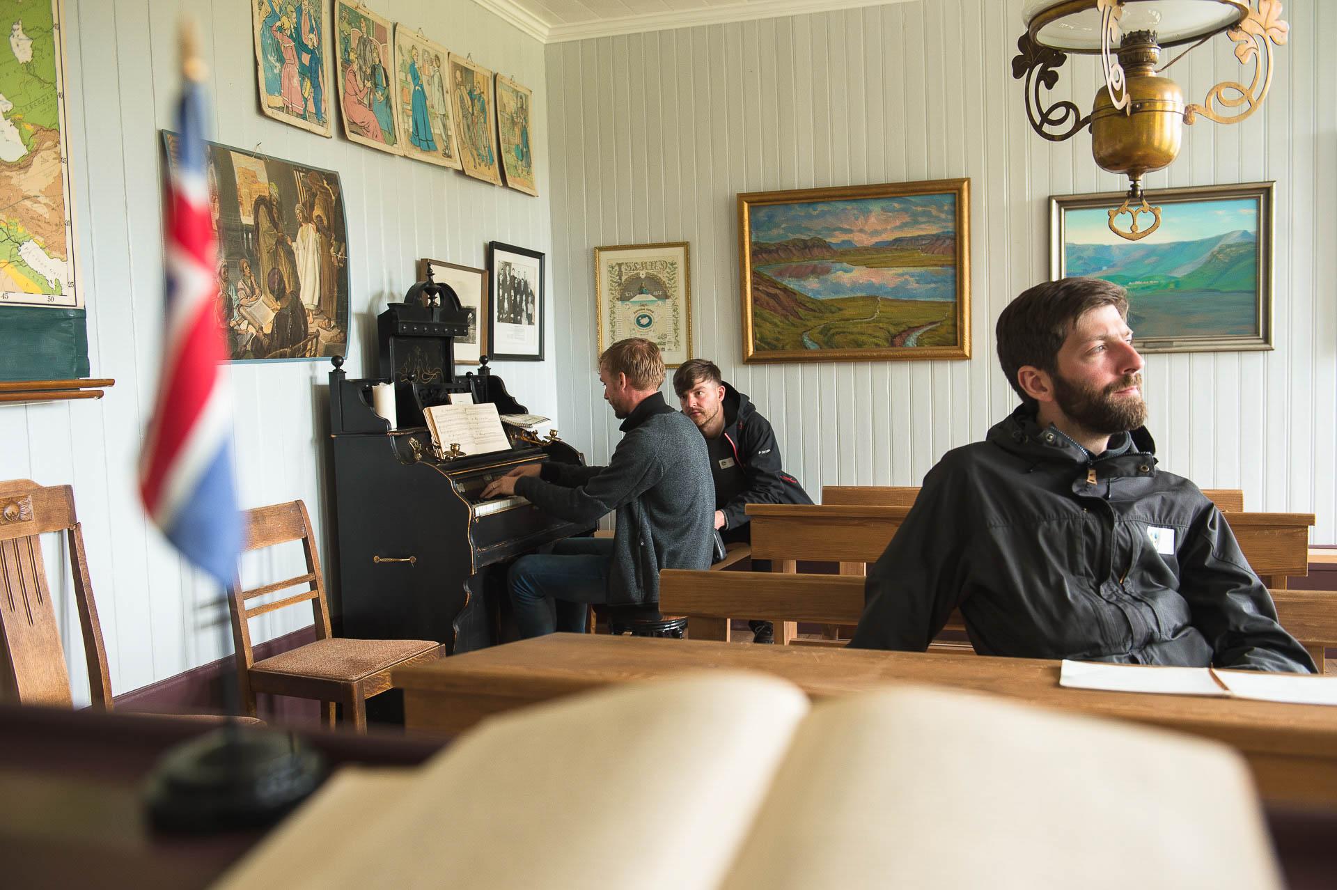 Fotostory von Redeleit und Junker - Ein Mann spielt Harmonium in Skógafsafn in Island