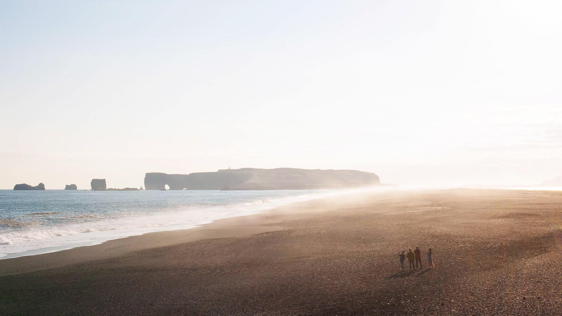 Fotostory Island von Redeleit und Junker - Eine Familie am Strand, im Hintergrund riesige Felsen im Meer
